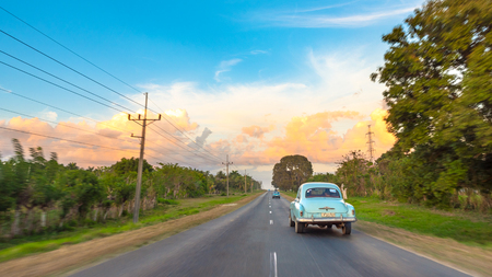 Cienfuegos, Cuba, vintage Chevrolet car driving in a rural road. Beautiful orange and blue colors contrasting in the afternoon sky