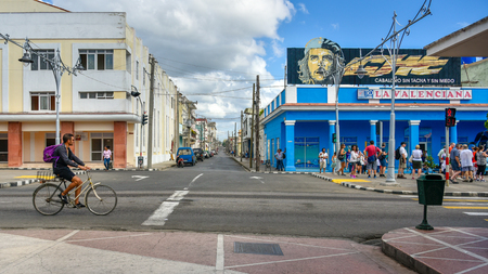 Cienfuegos, Cuba, El Prado everyday lifestyle of Cuban people.  A man rides in bicycle while a group of tourists look a Che Guevara sign on top of a store