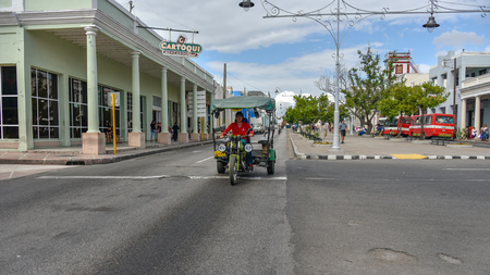 Cienfuegos, Cuba, a 'motoneta' driving in El Prado during the daytime. Typical mode of transportation in Cuban cities Stock Photo - 127003716