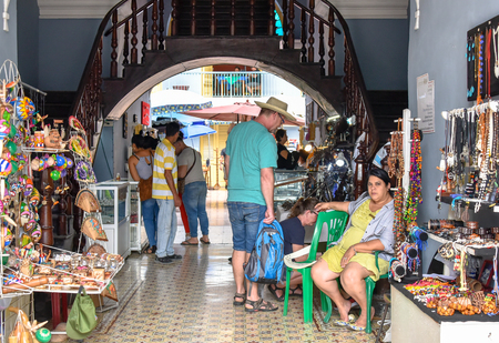 Cienfuegos, Cuba, tourists browsing a souvenir store while the employee sits on a chair. Lifestyle of Cuban people Editorial
