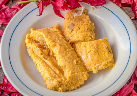 Delicious traditional Cuban tamal or tamales made from corn,  ready to eat, served fresh and hot on top of a white plate