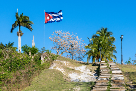 Low angle view of the Capiro Hill. There is a large Cuban flag waving in the wind. The place is a Cuban National Monument and a tourist attraction in the city