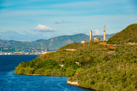 Santiago de Cuba, geographical feature of the city port. Island surrounded by water, with factory at end of road.