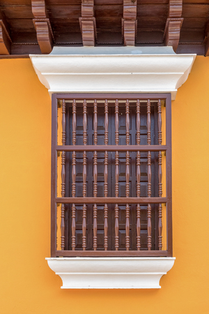 Old vintage Spanish colonial window, with wooden bars on front The wooden ceiling is on top. The wall is painted in orange and white colours