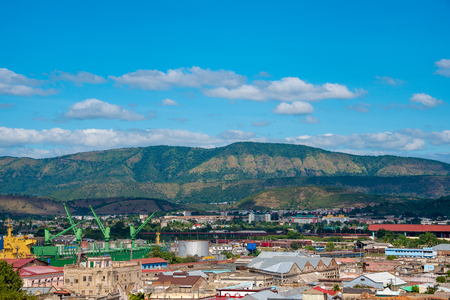 Santiago de Cuba, low rise city with Sierra Maestra mountains as background. View of a mountain range, with blue cloudy sky, and typical city architecture below. Reklamní fotografie
