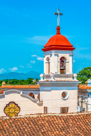 Cuba tourism: Presbyterian church near the main square in Sancti Spiritus, Cuba. It has a bell tower with the Holy cross on the top. Фото со стока