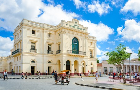 Teatro La Caridad architectural building with balcony  and people strolling through the street in front on a bright cloudy day Editorial