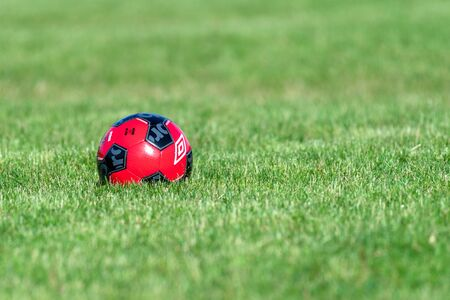 An Umbro soccer ball on a field of green color grass. The object has vibrant red and black colors. There are no people in the image
