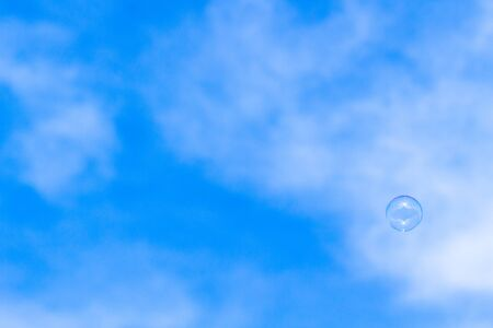 A soap bubble flying in the wind. A beautiful blue sky with some cloud formations serves as background. Stock Photo
