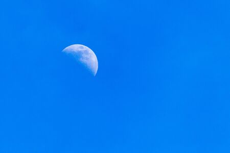 A zoom to the moon (Earths natural satellite) during the daytime. The sky is clear blue and there are no people in the vibrant color image Stock Photo