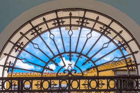 Santiago de Cuba, Iron work in old colonial window. Retro style architecture with a steel mosaic in front. Outside the window is a yellow house, and blue cloudy sky.
