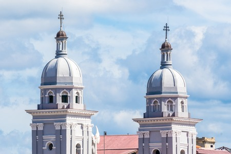 Santiago de Cuba, Catholic Cathedral Basilica Our Lady of Assumption. Two vintage gray towers of Catholic church in a cloudy blue sky