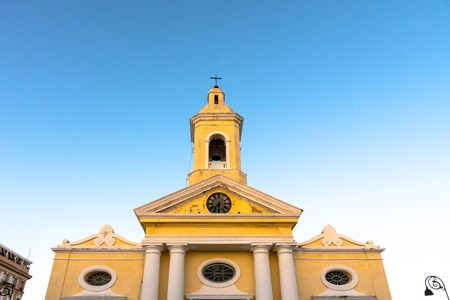 Facade of the colonial Roman Catholic Church in the city center. Low angle of the clock and bell tower. The place is a tourist attraction