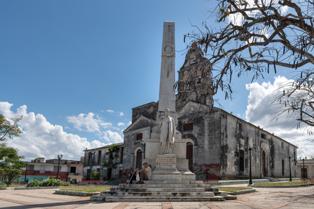 White marble monument honoring Miguel Jeronimo Gutierrez in the La Pastora park. The Catholic church of the same name is in the background. Miguel was a poet, journalist, and patriot born in this city