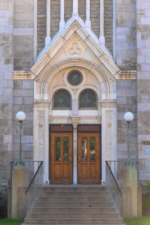 Montreal, Quebec, Canada-May 29, 2019: Chapel Notre-Dame de Lourdes. Architectural details of an old door. The vintage building has stone walls.
