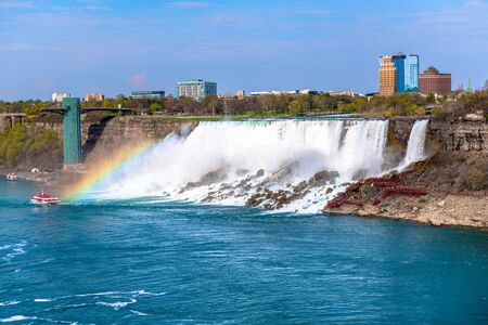 The American Falls with rainbow and the Hornblower cruise moving in the water. Point of view from the Canadian side of the border Stock Photo