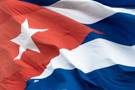 Close up of a Cuban flag waving in the wind. The image shows the red triangle, the star and part of the blue and white stripes. Stock Photo