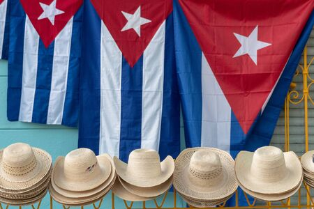 Cuban flags of different sizes and straw hats being sold as tourist souvenirs in the porch of a colonial style private house. Stock Photo