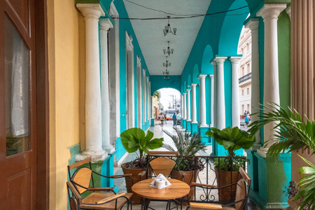 Colonial style architecture in the city center. The image is a point of view from the Hotel Central. The architecture has many columns and pastel colors. The area is a Cuban National Monument.