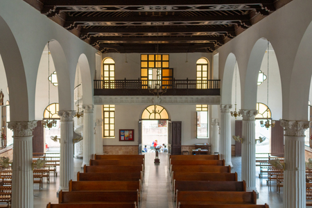 Indoors at the Buenviaje Catholic Church. High angle view from a balcony. The old colonial building has architectural arches and wood benches. The sunlight enters through doors and windows