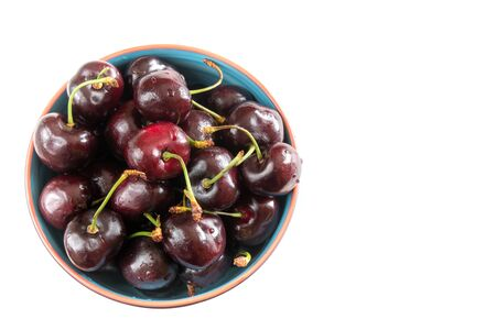 Red cherries served in a bowl over a white background.  The fruit is rich in antioxidants and anti-inflammatory compounds.
