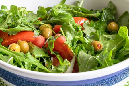 Close up of an arugula salad. The vegetarian food is mixed with pieces of tomatoes and olives. Healthy food green salad, Imagens - 128447590