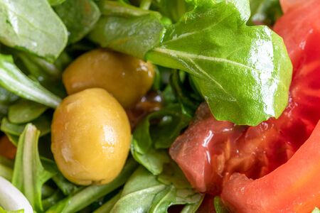 Close up of an arugula salad. The vegetarian food is mixed with pieces of tomatoes and olives. Healthy food green salad, Imagens