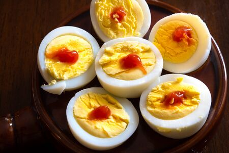 Boiled egg served with a spot of ketchup on top. The food is one of the most complete for humans. Its downside is being rich in cholesterol. Banco de Imagens