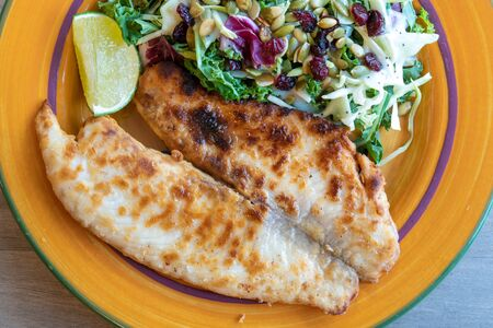 Healthy food, tilapia fillet served with a kale salad and a wedge of fresh lime. 写真素材