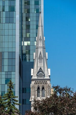 Architectural contrast in Montreal city, Canada. In the image, A modern building is compared to a colonial bell tower of a church