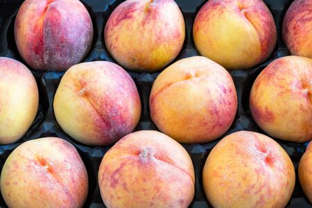 Large peaches forming a pattern inside of a box. Peaches are a healthy food because they are rich in potassium plus vitamins A, C, and E
