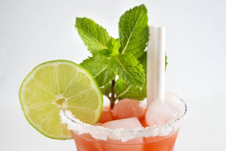 An alcoholic cocktail which main ingredient is tomato juice. The salty drink is garnished with a slice of lime and a mint sprig