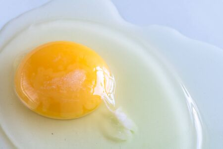 Close-up of a raw egg over a blueish plate. The whole food has a little salt on top and it is ready to be cooked