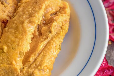 Delicious traditional Cuban tamal or tamales made from corn,  ready to eat, served fresh and hot on top of a white plate Tamale or tamales which is a corn dough-based traditional Latin American food.
