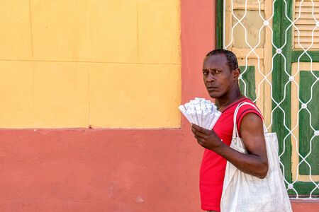 Santiago de Cuba, Cuba-July 5, 2019: Afro Caribbean man selling peanuts. Street seller in front of colorful wall and grilled window. After economic changes self employment is common in the island