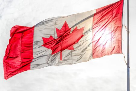 Canadian flag flying in the wind. The day is cloudy offering a light color background to the red and white ensign Фото со стока