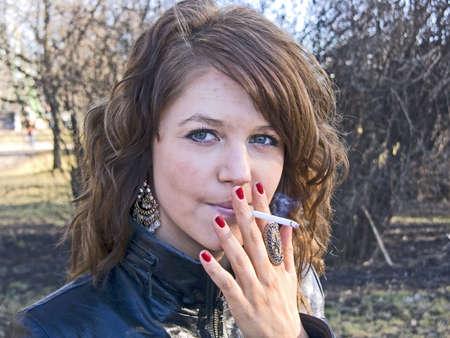 malos habitos: Ni�a bonita de fumar en el parque en d�a soleado