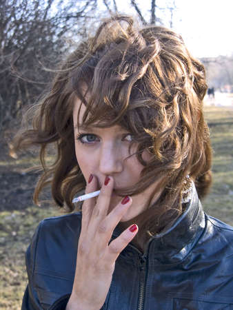 pretty girl smoking in the park in sunny day photo
