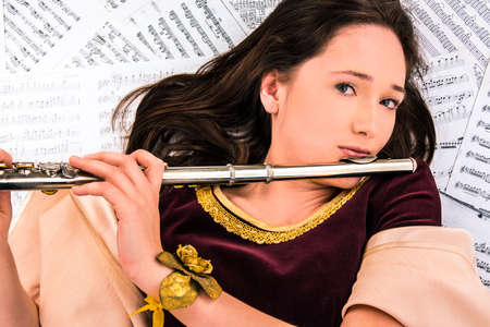 the girl in a brocade dress with a flute on the background of the notes photo