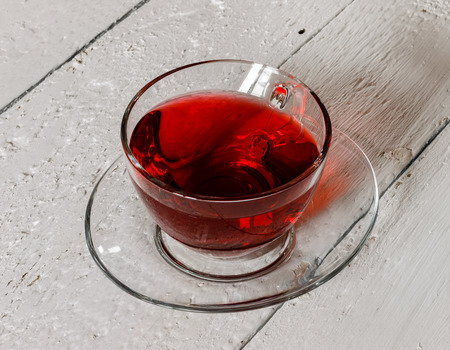 red tea: Cup of Karkadeh Red Tea on a white wooden table