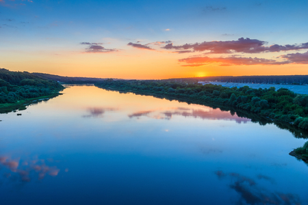 oka: sunset on the river embankment at summer evening with clouds and trees