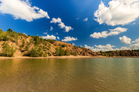quarry or lake or pond with sandy beach, water, trees and hills with cloudly sky at summer season