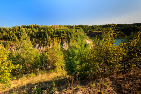 ravine: quarry or lake or pond with sandy beach, green water, trees and hills with blue sky at summer season