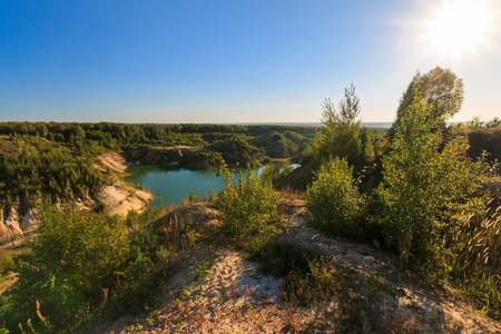 quarry or lake or pond with sandy beach, green water, trees and hills with blue sky and sun at summer season Stock Photo