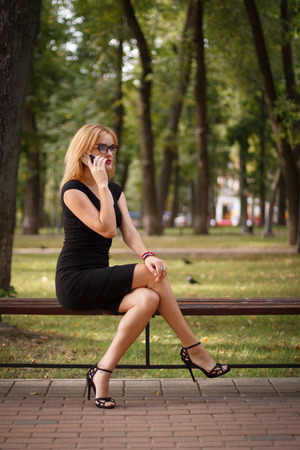 glases: blonde woman at black dress and glases talking on a mobile phone and sitting on a bench