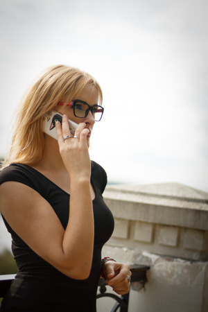 glases: blonde woman at black dress and glases talking on a mobile phone outdoors