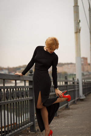 only women: beautiful blonde girl in a black dress corrects red shoes on the bridge Stock Photo
