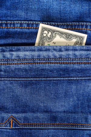 Two dollar bill in the pocket of  blue jeans. Cash money. Stock Photo