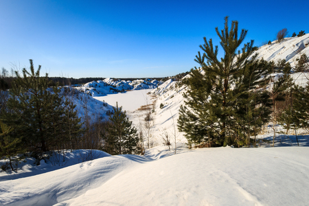Hills covered with snow in winter with pines, trees and blue sky background. Stock Photo
