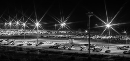 New cars parked at distribution center automobile factory at night with lights.